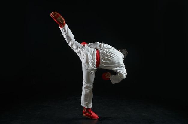 Mannelijke karateka, vechtersoefening in witte kimono en rode handschoenen, gevechtshouding. man op karatetraining, vechtsporten, training voordat de concurrentie wordt bestreden