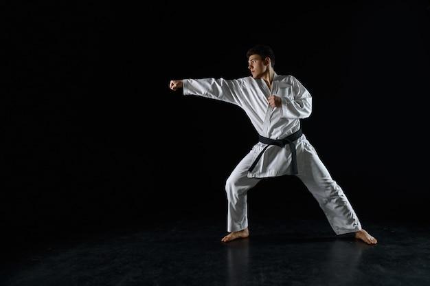 Mannelijke karatevechter in witte kimono, gevechtshouding. man op karatetraining, vechtsporten, vechtwedstrijd