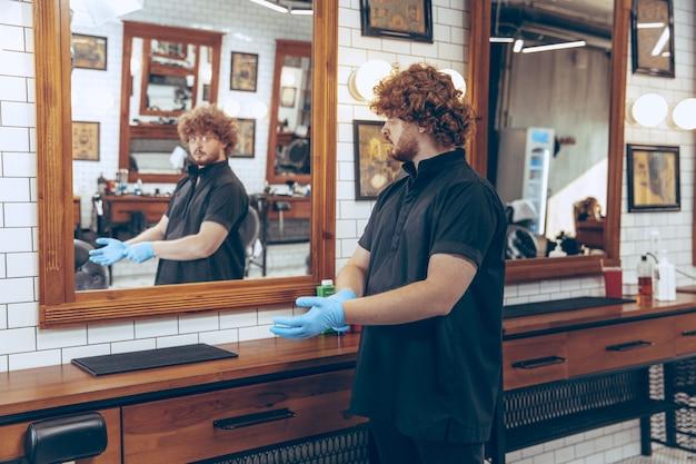Mannelijke kaukasische kapper bij de kapperszaak die handschoenen draagt die werkplaats voor cliënt voorbereiden. professionele kapper die handschoenen draagt. covid-19, schoonheid, zelfzorg, stijl, gezondheidszorg en geneeskundeconcept.