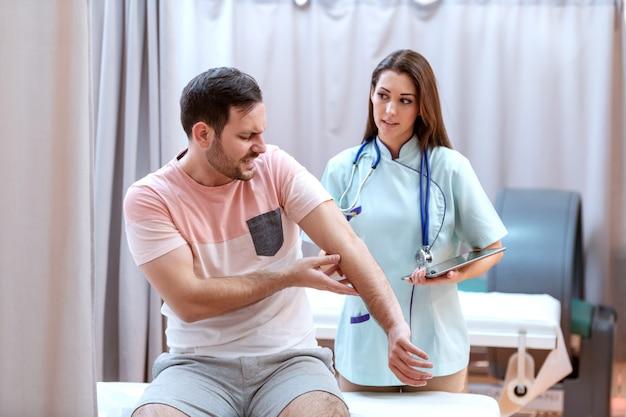 Mannelijke kaukasische patiënt in pijn die aan arts het kwetsen plaats toont. de tablet van de artsenholding en het spreken aan patiënt.