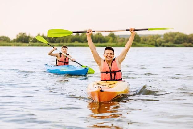 Mannelijke kayaker in kajak die zijn succes viert