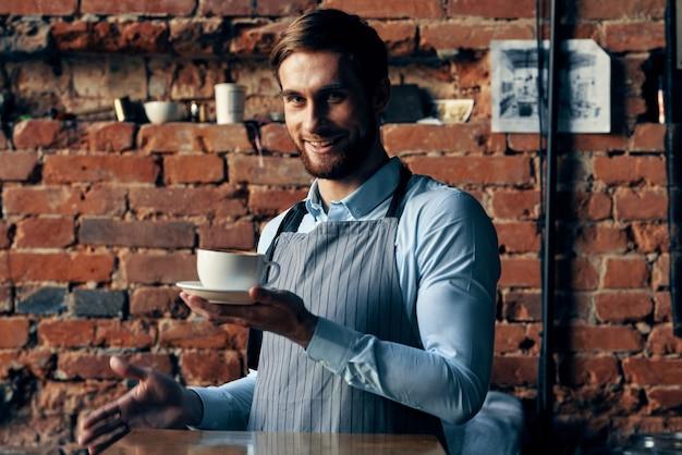 Mannelijke kelner die de levensstijl van de de dienstlevensstijl van de schortkoffiekop draagt