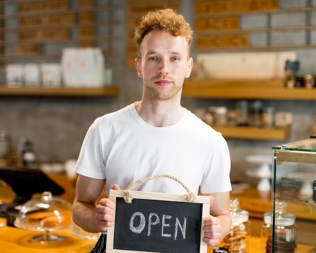 Mannelijke kelner die open teken voor koffiewinkel houdt