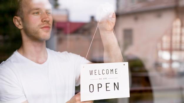 Mannelijke kelner die welkom teken op het venster van de koffiewinkel zetten