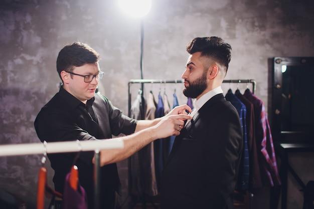 Mannelijke klant bij winkelcomplex die bedrijfskleren met winkelmedewerker het helpen proberen