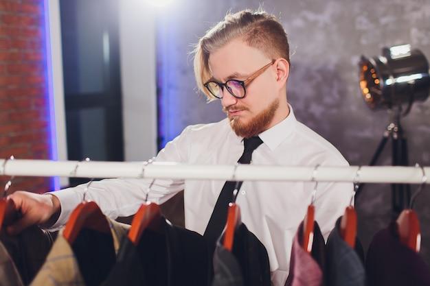 Mannelijke klant die een jasje in de opslag van de mensenkleren zoeken.