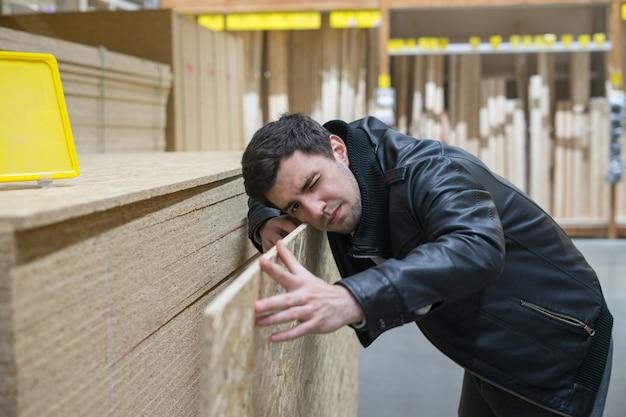 Mannelijke klant die flakeboard of oriented strand board osb kiest in de supermarkt. inkoop bouw en bouwmateriaal. de mens meet flakeboard.