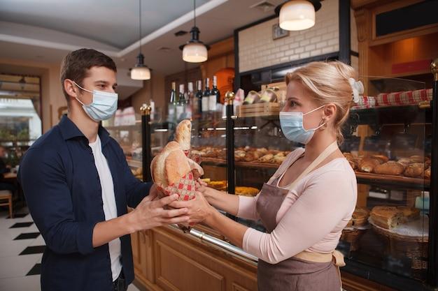 Mannelijke klant en vrouwelijke bakker die medische gezichtsmaskers dragen bij de bakkerij tijdens coronavirus-pandemie