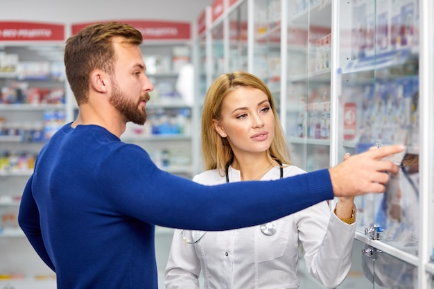 Mannelijke klant met een discreet gesprek met drogist in de apotheek