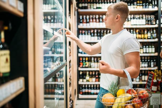 Mannelijke klant met mand die bier in supermarkt kiest. winkelen in voedselwinkel, alcoholsectie op achtergrond