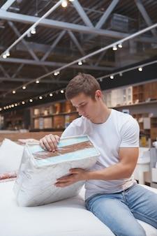 Mannelijke klant orthopeic matras te onderzoeken, meubels winkelen
