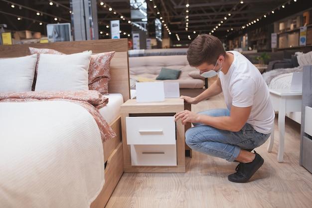 Mannelijke klant slaapkamermeubilair bij winkel te onderzoeken