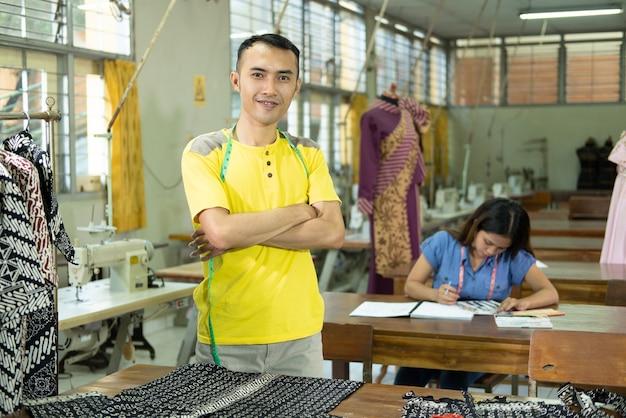 Mannelijke kleermakers smiley met gekruiste hand die zich in de productieruimte van de kledingstukconvectie bevindt