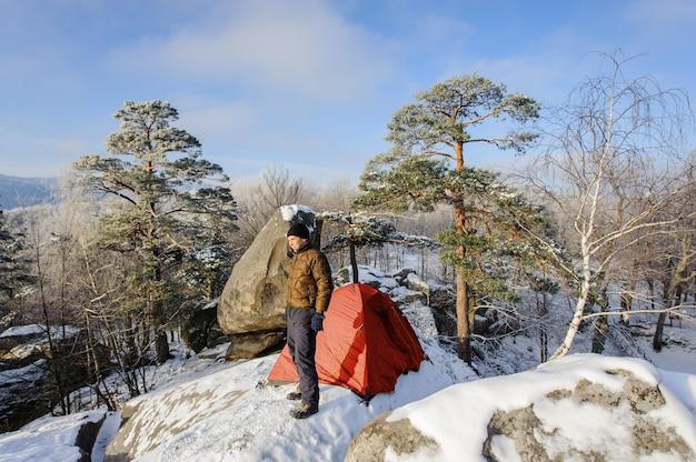 Mannelijke klimmer bijna zijn tent op de top van de rots