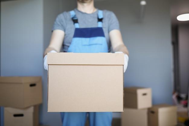 Mannelijke koerier houdt grote kartonnen doos vast