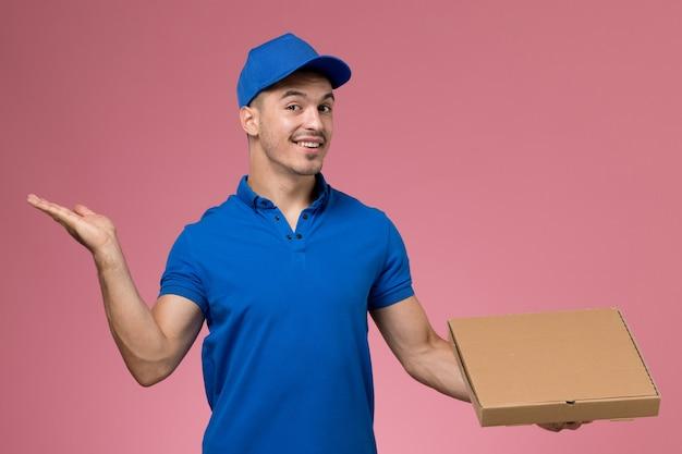 Mannelijke koerier in blauw uniform bedrijf bezorgdoos met voedsel met glimlach op roze, werknemer uniforme dienstverlening