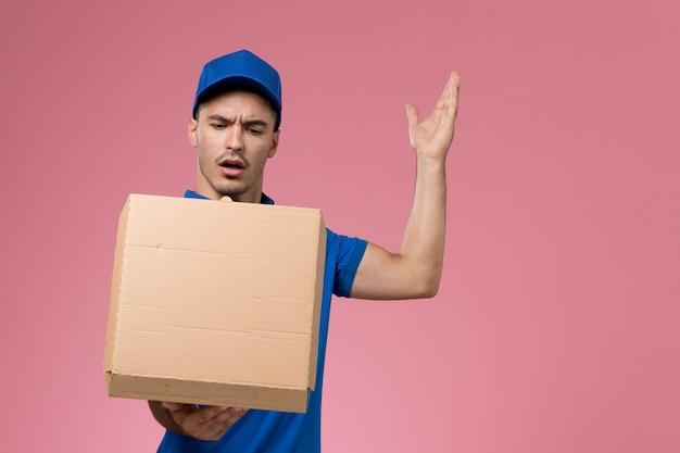 Mannelijke koerier in blauw uniform bedrijf bezorgdoos met voedsel op roze, uniforme dienstverlening
