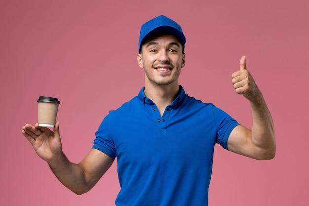 Mannelijke koerier in blauw uniform bedrijf levering koffiekopje glimlachend en poseren op roze, uniforme baan werknemer dienstverlening