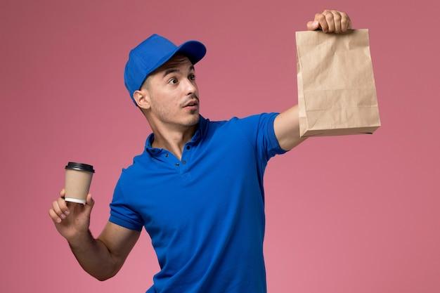 Mannelijke koerier in blauw uniform bedrijf levering koffiekopje voedselpakket op roze, uniforme werknemer dienstverlening