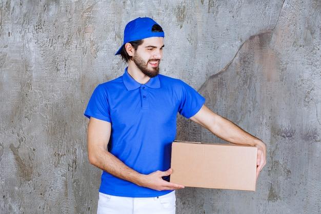 Mannelijke koerier in blauw uniform met een kartonnen afhaaldoos.