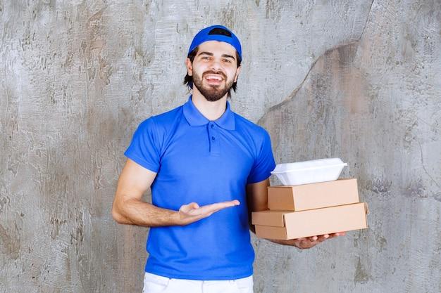 Mannelijke koerier in blauw uniform met kartonnen en plastic dozen.