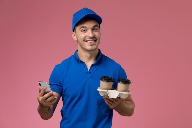 Mannelijke koerier in blauw uniform met koffiekopjes met behulp van zijn telefoon op roze, baan werknemer uniforme dienstverlening