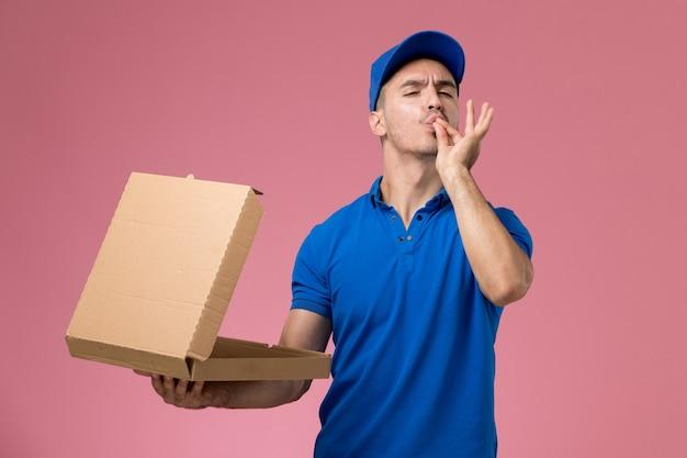 Mannelijke koerier in blauwe uniforme levering voedseldoos op roze, uniforme dienstverlening
