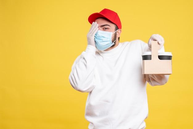 Mannelijke koerier in masker met bezorgkoffie op geel
