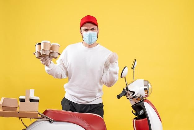 Mannelijke koerier in masker met koffie op geel holding