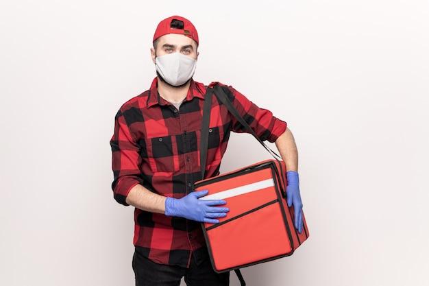 Mannelijke koerier in pet, rode flanel, beschermend masker en handschoenen met grote tas met bestellingen van klanten van café tijdens het werken in quarantaineperiode