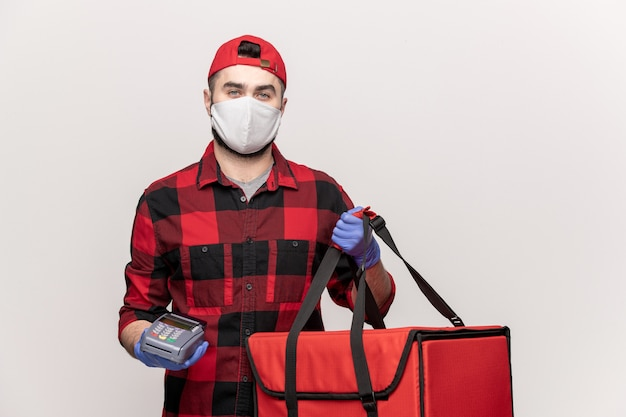 Mannelijke koerier in rode pet, flanel, beschermend masker en handschoenen draagtas met bestellingen en betaalautomaat tijdens werk in quarantaineperiode