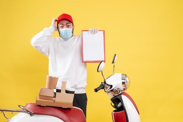Mannelijke koerier in steriel masker met dossieropmerking op geel