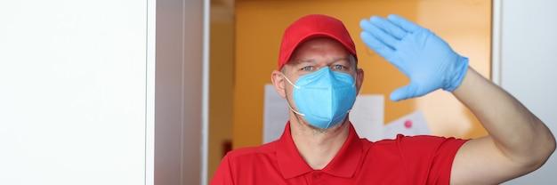 Mannelijke koerier met beschermend medisch masker en rubberen handschoenen met cadeau