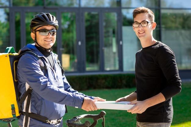 Mannelijke koerier met fiets en thermische zak die pizzadoos geven aan klant op straat dichtbij het kantoor