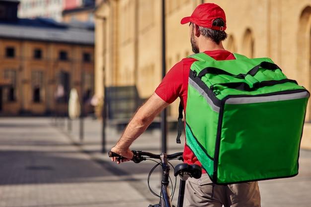 Mannelijke koerier met koelkasttas op de fiets
