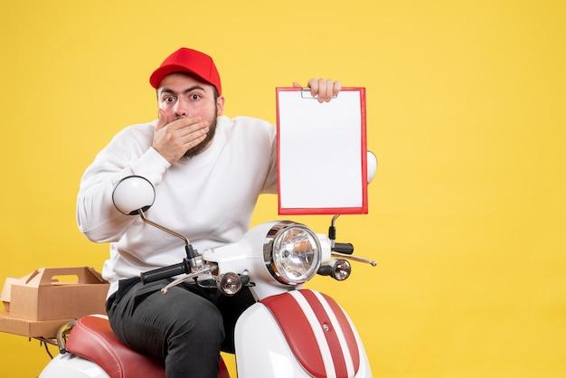 Mannelijke koerier op de fiets met dossiernota op geel bureau werk uniforme werknemer kleur bezorgservice baan
