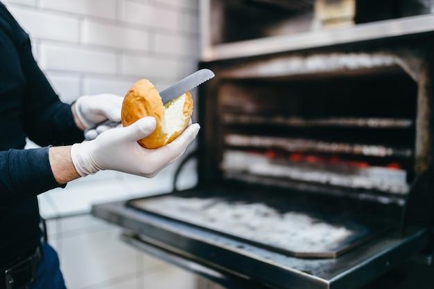 Mannelijke kok bereidt brood voor hamburger, koken op de grilloven