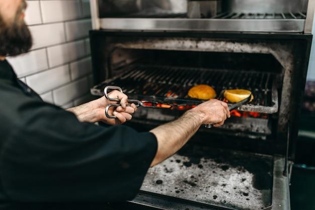 Mannelijke kok bereidt smakelijke hamburger op de grilloven.
