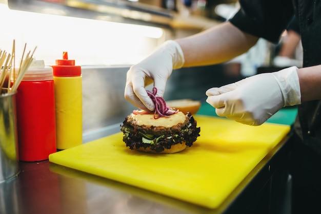 Mannelijke kok bereidt verse salade voor hamburger
