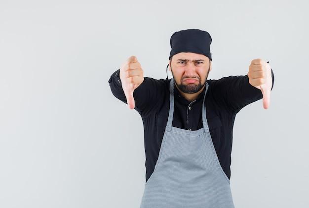 Mannelijke kok die dubbele duimen in overhemd, schort toont en teleurgesteld kijkt. vooraanzicht.