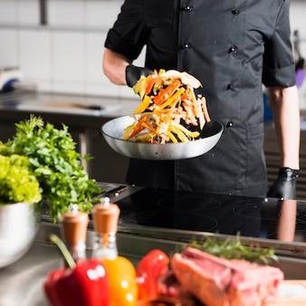 Mannelijke kok die groenten in pan werpt