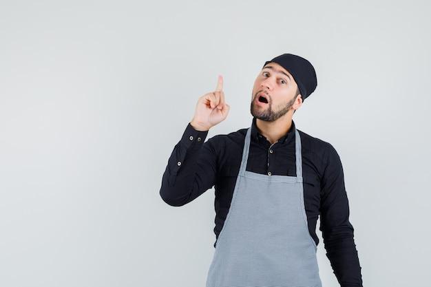 Mannelijke kok die in overhemd, schort benadrukt en nieuwsgierig kijkt. vooraanzicht.