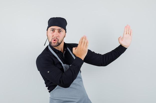 Mannelijke kok die karatekarbonade in overhemd, schort toont en boos kijkt. vooraanzicht.