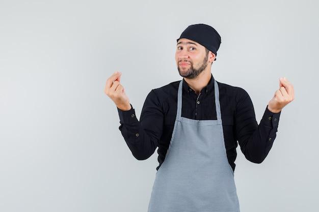 Mannelijke kok die met vingers in overhemd, schort gebaart en vrolijk, vooraanzicht kijkt.