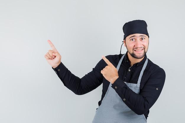 Mannelijke kok die omhoog wijst en in overhemd, schort, vooraanzicht glimlacht.