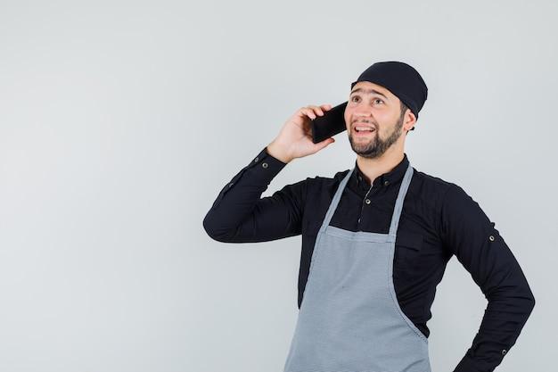 Mannelijke kok die op mobiele telefoon in overhemd, schort spreekt en vrolijk, vooraanzicht kijkt.