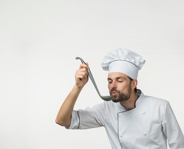Mannelijke kok die smakelijke soep van gietlepel ruikt die op wit wordt geïsoleerd
