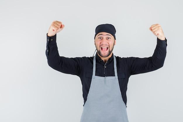 Mannelijke kok die succesgebaar in overhemd, schort toont en zalig, vooraanzicht kijkt.