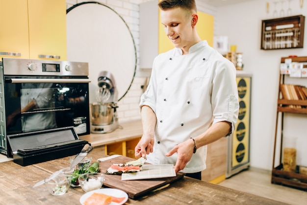 Mannelijke kok die sushi, aziatische keuken maakt