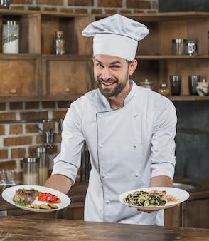 Mannelijke kok die zich in keuken bevindt die heerlijke schotel voorstelt